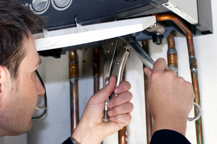 Plumber using a spanner to repair a tankless water heater