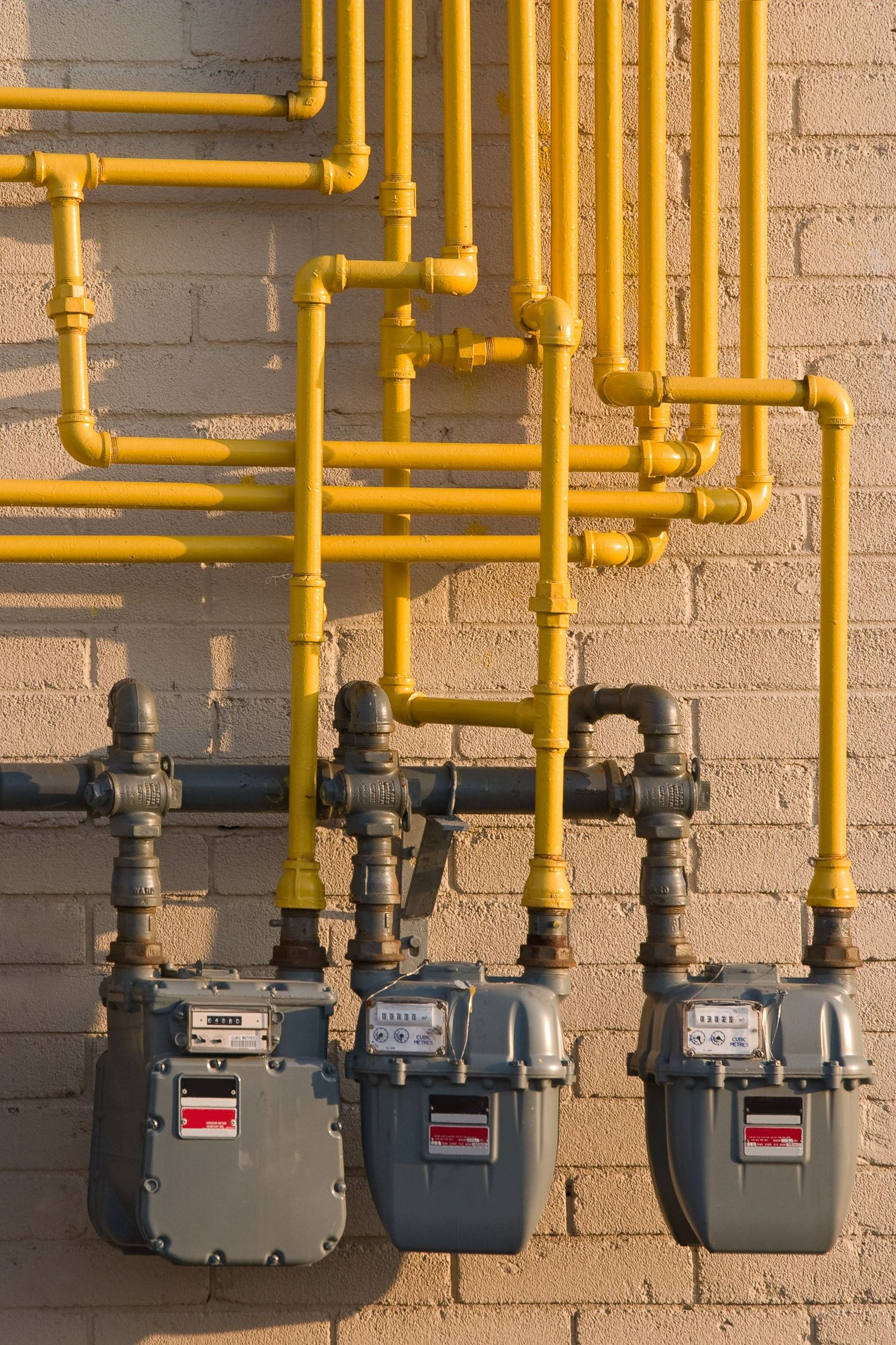 commercial gas meters with yellow gas lines running upwards