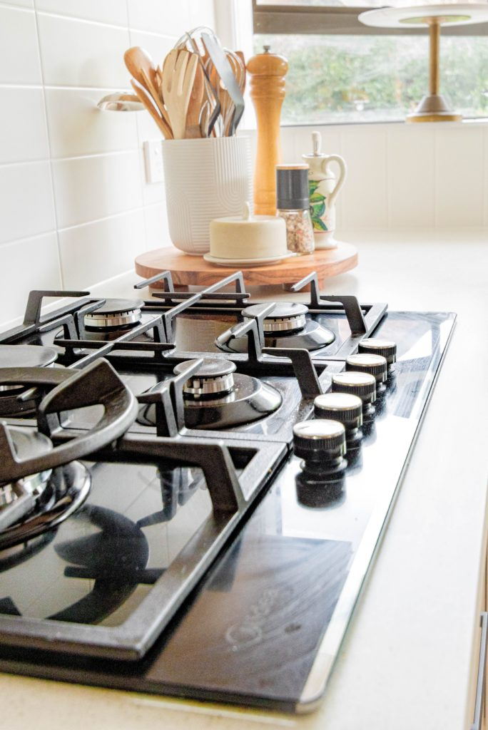 four burner stainless steel residential stove that is powered by natural gas
